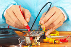 Master measures the parameters of the electronic device with multimeter Royalty Free Stock Photography