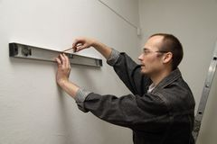 Master measures the wall. Man working level. Master measures the wall Royalty Free Stock Photo