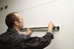 Master measures the wall. Man working level. Master measures the wall Stock Photos