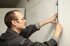 Master measures the wall. Man working level. Master measures the wall Royalty Free Stock Image