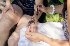 Master mehndi draws henna on a female hand Stock Images