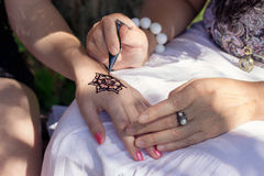 Master mehndi draws henna on a female hand Stock Photography