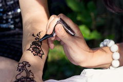 Master mehndi draws henna on a female hand Royalty Free Stock Images