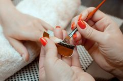The master of the nail polish puts a fixative on the finger before making the nails gel in the beauty salon. Professional care for hands royalty free stock image