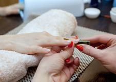 The master of the nail polish puts a fixative on the finger before making the nails gel Stock Photos
