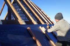 The master nails the bars, fixing this gidrorizer to the rafter, the blue sky appears on the background stock photos