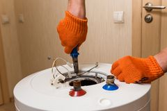 Plumber hands tighten bolts of water heater. Master in orange gloves fix elements of boiler indoors royalty free stock photos