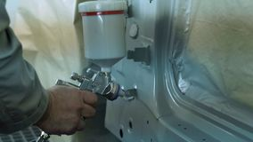 Master paints the body of the spray gun in a car workshop stock video footage