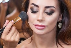The master paints a brush of powder on the girl`s face, completes the day`s make-up. In the beauty salon. Professional skin care stock photo