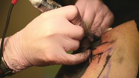 The master paints a tattoo with a drawing of death on the shoulder of a man stock video