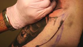 The master paints a tattoo with a drawing of death on the shoulder of a man stock footage