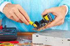 Master parses electronic hardware for repair in service workshop Royalty Free Stock Images