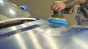 Master polishes the deep blue sport car via polish mashine in a car workshop Royalty Free Stock Images