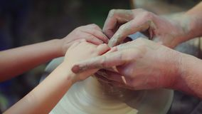 Master potter teaches the child his skill. The concept is the transmission of experience by generations stock video footage