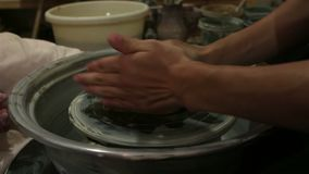 The master creates a white clay product. The master`s hands close-up sculpt a clay product using a potter s wheel.