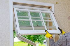 Master removes old home repairs, replacement windows. Home repairs, replacement windows. Master removes old window royalty free stock photography