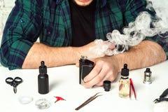 Master repair ecigarette on the white table. Maintenance of electronic mod vaping device.Modern vaporizer. Start vaping safe ecig vape. Master repair ecigarette stock images