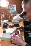 The master repairs the microplate under a microscope royalty free stock photo