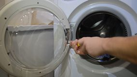 Master repairs washing machine with a screwdriver stock video footage