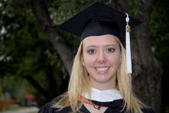 Master's Degree Graduate. A photo of a young woman in a cap and gown after graduation. Photo has copy spac stock photography