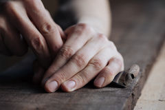The master`s hands work with a wooden surface, a professional does wood crafts. Wood carving, the master`s hands work with a wooden surface, a professional does stock photos