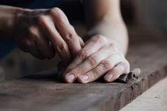The master`s hands work with a wooden surface, a professional does wood crafts. Wood carving, the master`s hands work with a wooden surface, a professional does Stock Image