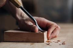 The master`s hands work with a wooden surface, a professional does wood crafts Royalty Free Stock Photos