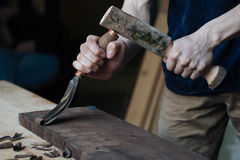 The master`s hands work with a wooden surface, a professional does wood crafts. Wood carving, the master`s hands work with a wooden surface, a professional does Royalty Free Stock Photography