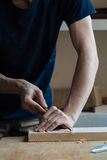 The master`s hands work with a wooden surface, a professional does wood crafts. Wood carving, the master`s hands work with a wooden surface, a professional does royalty free stock images