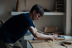 The master`s hands work with a wooden surface, a professional does wood crafts. Wood carving, the master`s hands work with a wooden surface, a professional does Stock Images