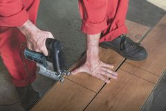 Master saws the bar with an electric saw. A worker in a red jumpsuit cuts a laminate with a jigsaw by marking, resting his foot on the bar. Master saws the bar royalty free stock photography