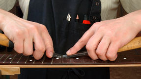 Luthier removes the frets of the guitar neck. Luthier removes worn frets of the guitar neck producing electric repair stock photos