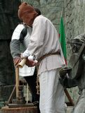 Master and servant. Servant of knight helps his master to prepare the weapon royalty free stock images