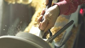 Master sharpening on a lathe wood. Master slowly carving chisel candlestick on a lathe stock footage