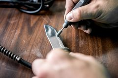 Sharpening the knife on special equipment to make it very sharp stock photo
