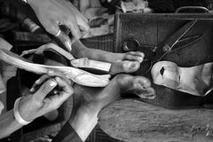 The master in the shoe shop. Manually sews a strap of sandals. India Royalty Free Stock Image