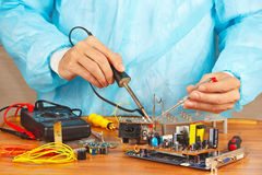 Master solder electronic components of device in service workshop Royalty Free Stock Photo