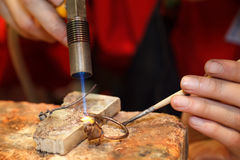 Master soldering jeweller ornament. Picture of hands and product close up Stock Image