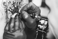 Master tattoo woman on her back. Tattooer showing process of making a tattoo hands holding a tatoo machine stock photo
