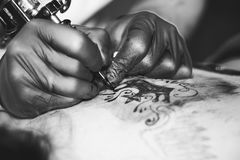 Master tattoo woman on her back. Tattooer showing process of making a tattoo hands holding a tatoo machine stock images