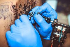 Master tattoo woman on her back. Tattooer showing process of making a tattoo hands holding a tatoo machine royalty free stock photography