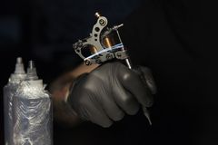 The master the tattooer holds in hand the machine on a black background royalty free stock photos