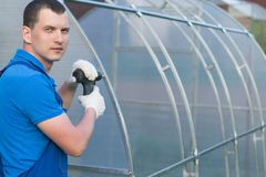The master with the tool collects a greenhouse in the street royalty free stock images