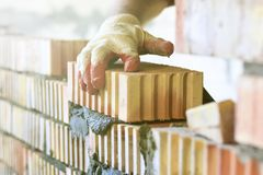 Master with a tool, stacks a red brick. there is illumination and toning. shallow depth of cut.  royalty free stock image