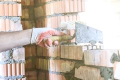 Master with a tool, stacks a red brick. there is illumination and toning. shallow depth of cut.  royalty free stock photo