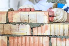 Master with a tool, stacks a red brick. there is illumination and toning. shallow depth of cut.  stock images