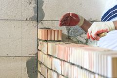 Master with a tool, stacks a red brick. there is illumination and toning. shallow depth of cut.  stock photos