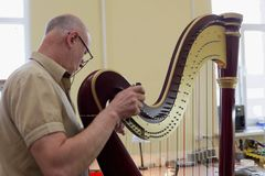 Master tuning the harp Stock Images