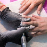 The master uses an electric machine to remove the nail polish on the hands during manicure in the salon. Hardware manicure. Concep Stock Image