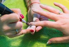 The master uses an electric machine to remove the nail polish on the hands during manicure in the salon. Hardware manicure. Concep Royalty Free Stock Photography